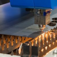 The fiber laser cutting machine  cutting the sheet metal with the sparking light.New technology manufacturing process.